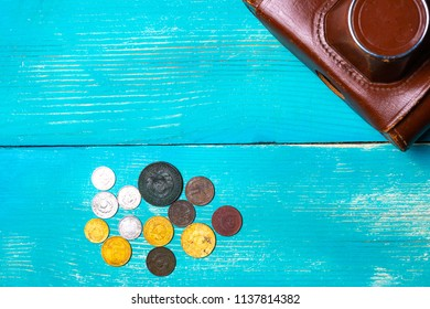 part of the old film camera in a leather case on a wooden table is next to the iron old coins of the USSR, the past time