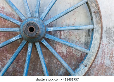 Part of old ironed blue wagon or carriage wheel on old wall with peeling paint