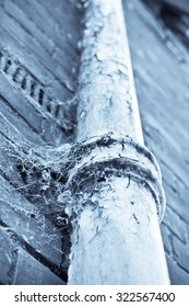 Part of an old metal pipe on a brick wall, with cobwebs, in blue monochrome tones