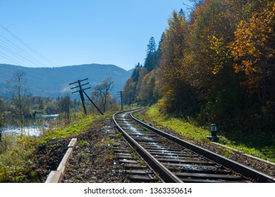 Part of the old railway and old power line support near the forest and mountains. It was autumn weather and blue sky.
