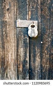 Part of an old wooden door with a metal padlock