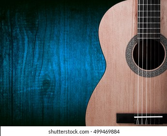 Part of a orange acoustic guitar on wooden background