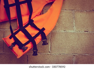 part of orange life jacket  lean on block wall ,vintage tone