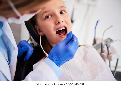 Part of orthodontist examining child's teeth in dentist's office