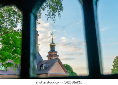 Part of an orthodox church with a dome and a cross close-up over a fence against a blue sky. Orthodox cross
