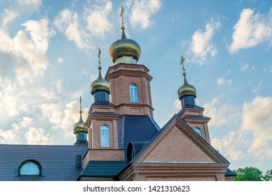 Part of the Orthodox Church with four domes and crosses close-up against the blue sky. Orthodox cross
