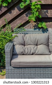 Part of a patio with modern garden furniture. Wicker rattan sofa near wooden fence and green bushes. Vertical view, outside