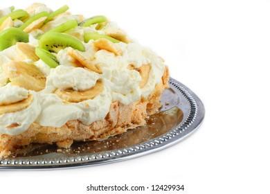 part of pavlova cake with banana and kiwi over  metal dish over white