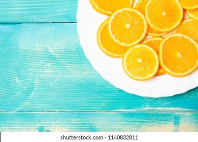 part of a plate of fruit orange sliced rings, plate on a blue background