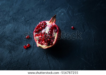 Part of pomegranate with seeds on black stone background.