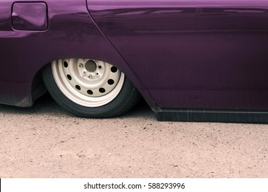 Part of a purple car with pneumatic suspension on the pavement