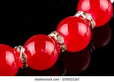Part of red pearl bracelet against black background