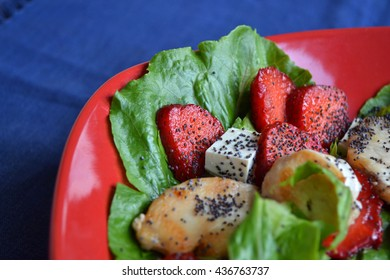 A part of red plate of salad with  slices of roast turkey, fresh  ripe strawberry,pieces of feta cheese, green salad and poppy seeds. Healthy summer dinner dish. Mix of meat, vegetables and fruit .