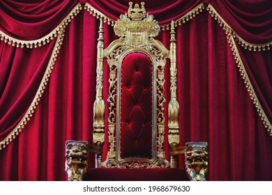 Part of the red royal chair against the background of red curtains. A place for a king. Throne