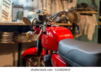 Part of red vintage retro motorcycle parked in the garage, close-up