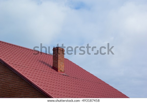 Part of the red-tiled roof of one of the private houses.