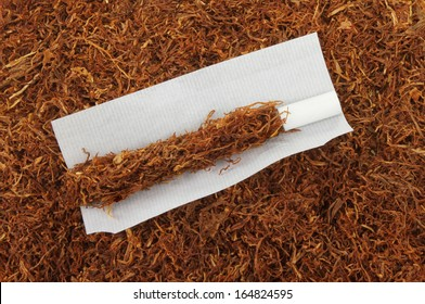 Part rolled cigarette on a background of tobacco