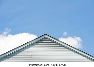 part of the roof and wall lined with white siding against the blue sky
