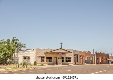Part of Route 66 with a former service station on the corner and other businesses along the main drag of a one way street in a small town