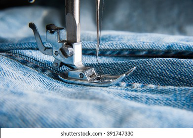 Part of sewing machine and jeans cloth closeup