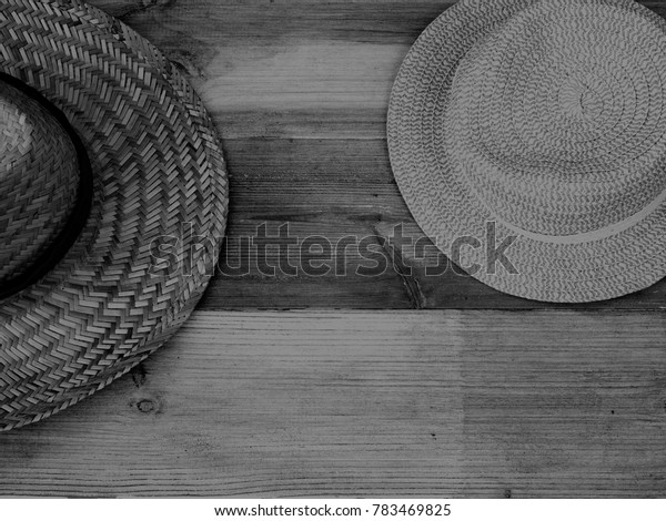 A Part Shown Trilby Hat and a Part Shown bonnet Hat Showing the Wicker Weave on a Black and White Wood Background