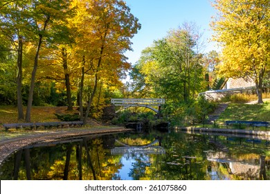 A part of Small Lake with reflection of trees in water, in a Park of Montreal in Autumn, and little Bridge in Background