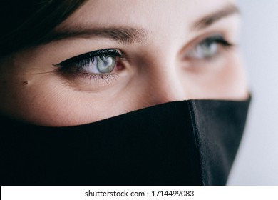 part of smiling face of a young beautiful woman in a black stylish mask, fashion and lifestyle 2020 under quarantine and epidemic, concept of science and positive looj future