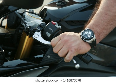 part of a sport bike close up. man's hand turned off the clutch on a motorcycle close up. biker hand on motorcycle handlebar