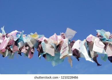 Part of a string of cloth bunting under a blue sky