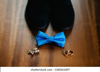 Part stylish men black shoes, wedding two rings, cufflinks and bow tie lying on a light brown table. Wedding accessories groom on rustic wooden background. idea composition.