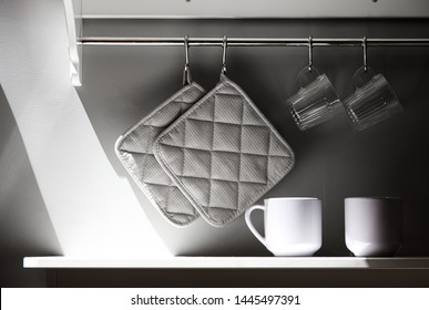 Part of the sunny kitchen with a gray wall. Shelf with glasses and railing with napkins