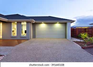 Part of this luxury house includes a garage with a white door and illuminated by two small lights under the ceiling.
