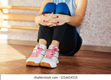 Part of tired woman who sits on a floor after the training in the fitness studio.