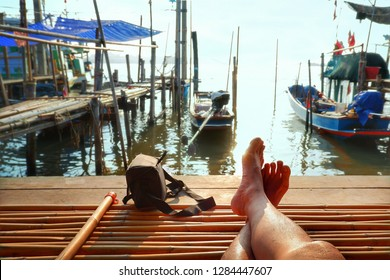 Part of tourist's leg in relaxing gesture and camera bag on bamboo litter with traditional fishing boats moored over seaside view and sunrise sky background at homestay in ecotourism concept