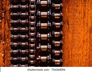 Part of a Used Automotive Gear Chain n a Wooden Background