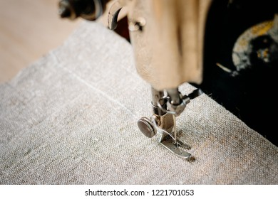 Part of vintage hand sewing machine and item of clothing. Steel needle with looper and presser foot close-up.