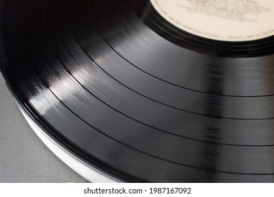Part of vinyl record playing on old turntable. Detail of vinyl LP showing texture and music tracks