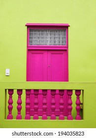 Part of the wall of the house. Door to balcony. Bright colors. Deep pink and yellow-green. Bo-Kaap. Malay Quarter. Cape Town. South Africa