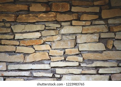 part of the wall is made up of individual pieces of stones in cement, the dark upper part is gradually lighter down, yellow and brown shades,
