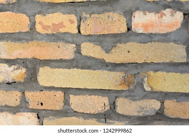 Part of the wall of refractory bricks peach color with concrete seams