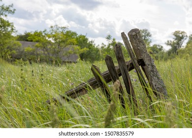 Part of a weathered wooden fence overgrown with grass