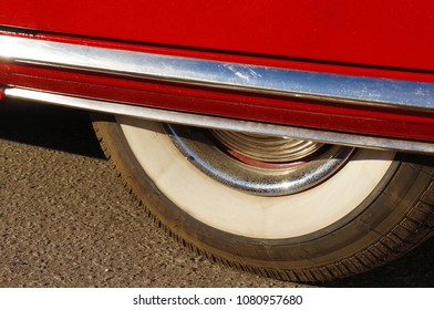 Part of the wheel of a red car