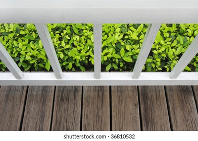 Part of white balcony,wood floor and bush.