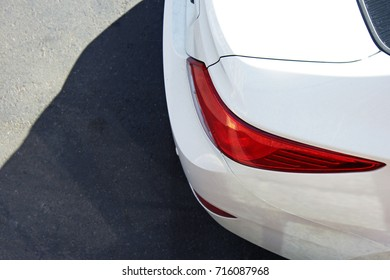 Part of a white car on a background of asphalt. Car headlights.