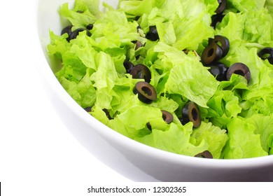 part of white dish with a fresh green lettuce and slices of olives over white