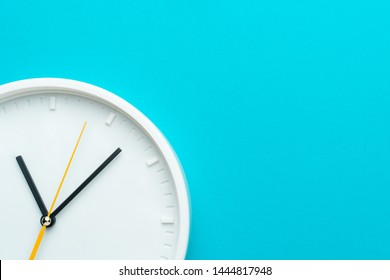 Part of white wall clock with yellow second hand hanging on wall. Close up image of plastic wall clock over turquoise blue background with copy space. Photo of time management or time is going concept