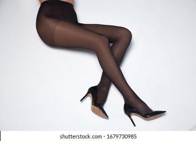 Part of woman body perfect shape legs feet skin tan wear stockings, nylons, pantyhose lingerie hosiery hose studio shot. on white background.