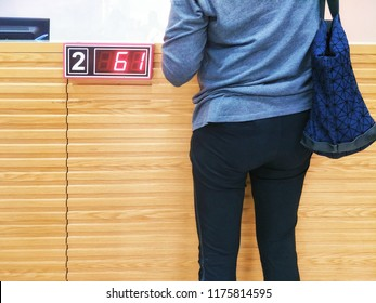 Part of woman in casual wear with bagpack is contacting financial transactions with numbers of queuing management system in wooden bar counter of bank, back side with space for your text
