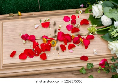 part of a wooden coffin while funeral - decdorated with red flower leaves and Christian cross