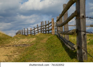 part of a wooden fence against the backdrop of Mount Petros. Carpathian landscape. Ukraine. The road between the two fences to the sky. Pasture for cows